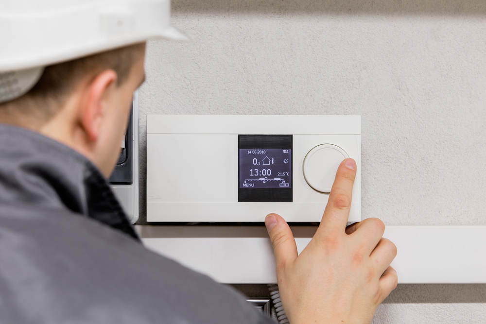 A technician adjusts HVAC controls in a home.