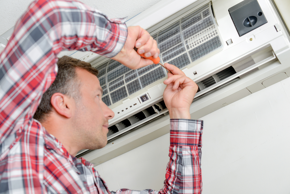 A man repairs his AC unit