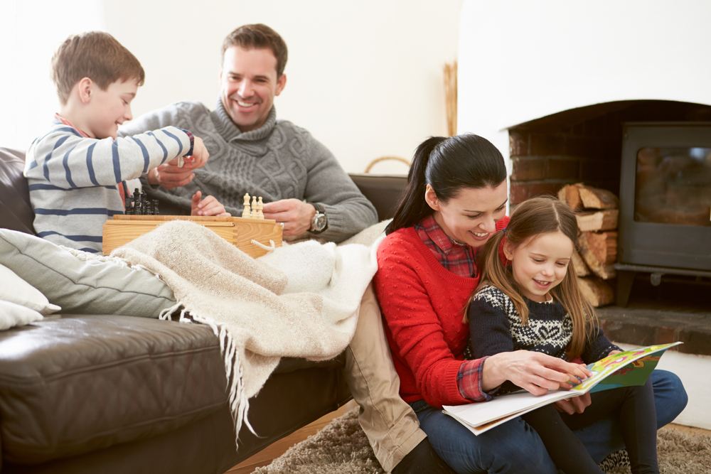 Parents play chess and read with their children by their fireplace